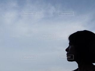 曇った空の前に立っている女性の写真・画像素材[3220829]