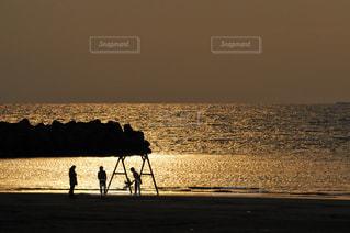 夕暮れの海岸とブランコで遊ぶ家族の写真・画像素材[3187654]