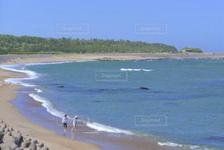 波打ち際を散歩するカップルの写真・画像素材[3316559]