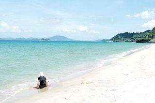 海の横にある砂浜に座る人の写真・画像素材[1023397]