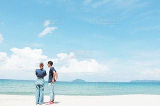 海の横にある砂浜のビーチの上に立っている人の写真・画像素材[1405798]
