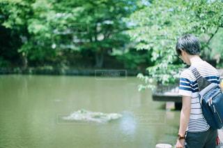 水の体の横に立っている人の写真・画像素材[727127]