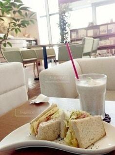 食べ物の皿と一杯のコーヒーをテーブルの上に置いての写真・画像素材[3307399]
