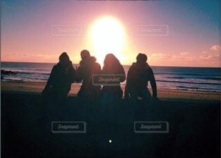 夕日の前に立っている人々のグループの写真・画像素材[3397559]