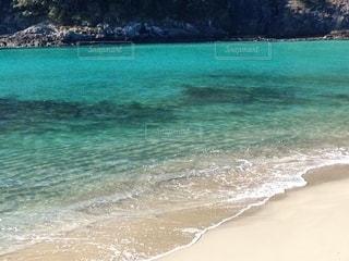 水の体の近くのビーチで人々のグループの写真・画像素材[3584977]