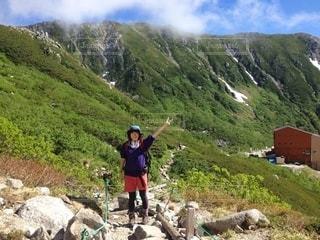 岩の丘の上に立っている男の写真・画像素材[3584984]