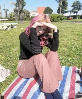 芝生で覆われた畑の上に座っている人の写真・画像素材[3184581]
