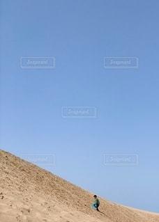 空と砂丘と男の子の写真・画像素材[3245121]