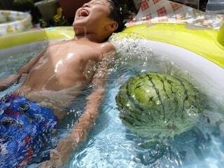 ビニールプールで寝転ぶ笑顔の男の子の写真・画像素材[4007909]