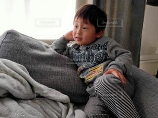 ソファでくつろぐ小さな男の子の写真・画像素材[4034347]