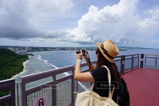 フェンスの隣に立っている人の写真・画像素材[3393057]