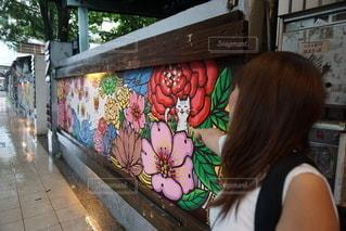 落書きで覆われた壁の前に立っている女性の写真・画像素材[3442159]