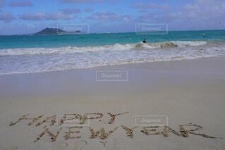 海の隣の砂浜の上に立っている人の写真・画像素材[3880682]