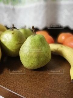 木製のテーブルの上に座っている果物のボウルの写真・画像素材[3200149]