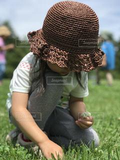 草の中に座っている小さな女の子の写真・画像素材[3205049]