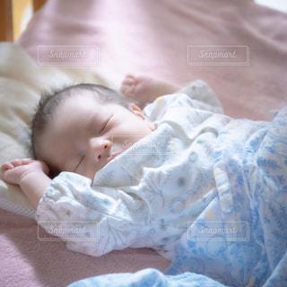 ベッドに横たわる赤ん坊の写真・画像素材[3220544]
