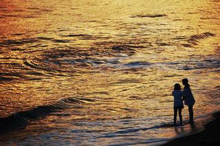 水域の隣に立っている男の写真・画像素材[2211154]