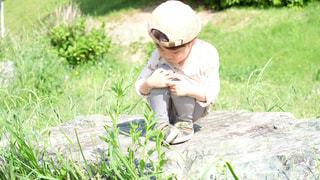 岩の上にひとり寂しく座る少年の写真・画像素材[3210458]