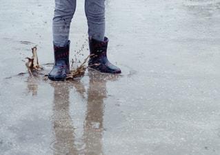 水溜りで遊ぶ少年の写真・画像素材[3229448]