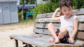 木製のベンチに座っている小さな男の子の写真・画像素材[3618390]