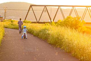 自然,空,春,自転車,屋外,親子,電車,夕暮れ,夕方,子供,オレンジ,河川敷,鉄橋,夕陽,川沿い,少年,お散歩,お父さん,追いかけっこ,えちぜん鉄道