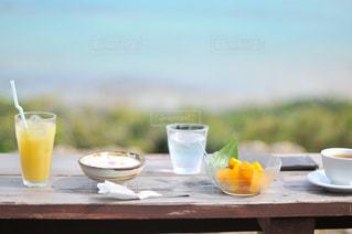 コーヒーとピクニック テーブルの上の水のガラスのカップの写真・画像素材[920366]