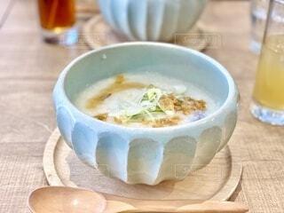 木製のテーブルの上に座っているスープのボウルの写真・画像素材[3856343]