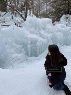 雪の山の隣に立っている人の写真・画像素材[3856351]