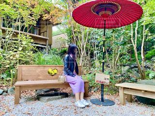 傘を持ってベンチに座っている人の写真・画像素材[3929609]