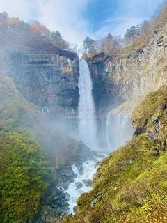 背景に山のある滝の写真・画像素材[3488039]