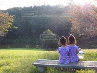 公園のベンチに座っている人の写真・画像素材[4586124]