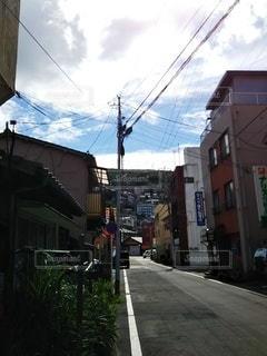 建物の脇に車が停まっている狭い街の通りの写真・画像素材[3229919]