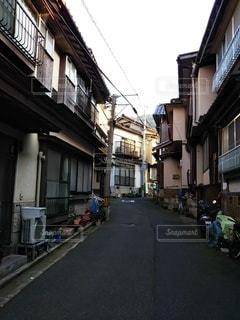 建物の脇に車が停まっている狭い街の通りの写真・画像素材[3229926]