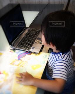 テーブルの上に座っているラップトップコンピュータを使っている少年の写真・画像素材[3285155]