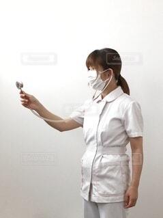 女性,風景,屋内,白,女,家,手持ち,人物,横顔,人,立つ,書類,シャツ,ポートレート,施設,女の人,制服,病院,熱,ライフスタイル,発熱,コロナ,入院,風邪,病気,マスク,手元,診察,インフルエンザ,パンツ,白バック,上半身,薬剤師,休む,1人,長い髪,看護師,ナース服,聴診器,患者,訪問看護,看護,検温,医療従事者