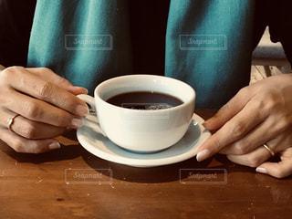 コーヒーを飲みながらテーブルに座っている人の写真・画像素材[3237822]