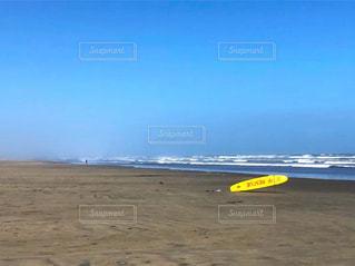 砂浜の上にある黄色いフリスビーの写真・画像素材[3244631]