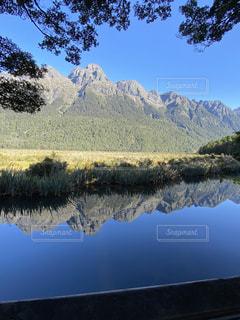 背景に山のある湖の写真・画像素材[3244034]