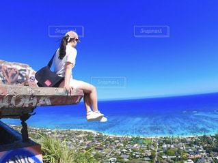 水の体の隣のベンチに座っている人の写真・画像素材[3249002]