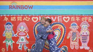 カラフルな色に囲まれて笑顔でハグするカップルの写真・画像素材[2378757]