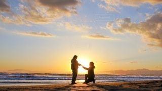 夕日をバックにプロポーズの写真・画像素材[3553535]