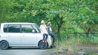 車の上に乗っている2人の写真・画像素材[3575201]