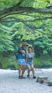 木のブランコではしゃぐカップルの写真・画像素材[3617158]