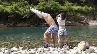 川に飛び込む夫婦の後ろ姿の写真・画像素材[3637917]