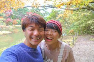 紅葉をバックにカメラに笑顔を向けるふたりの写真・画像素材[3870849]
