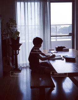 窓の前のテーブルに座っている男の写真・画像素材[3356909]