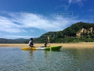 水の体でボートの後ろに乗っている男の写真・画像素材[3634418]