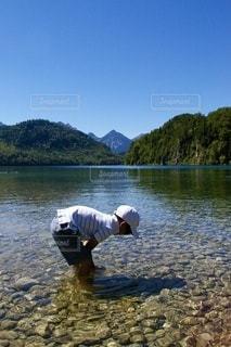 水の体の隣に立っている男の写真・画像素材[3634415]