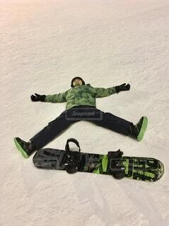 雪に覆われた斜面の下にスノーボードに乗っている人の写真・画像素材[3804521]