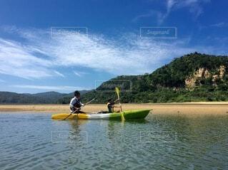 水の体でボートの後ろに乗っている男の写真・画像素材[3804517]